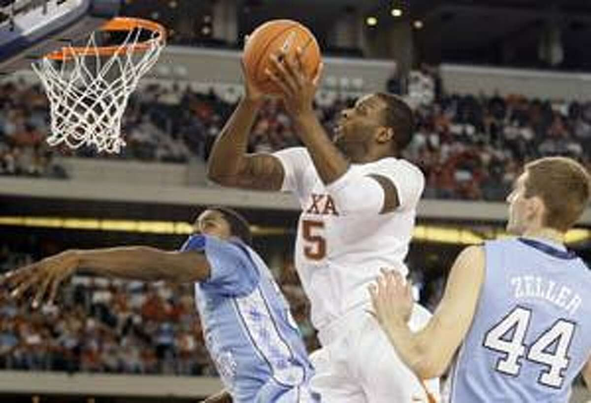 AP Texas guard Damion James (5) attempts a shot over North Carolina's Tyler Zeller (44) and Ed Davis, left, in the second half of a game, Saturday in Arlington, Texas. Texas won 103-90.