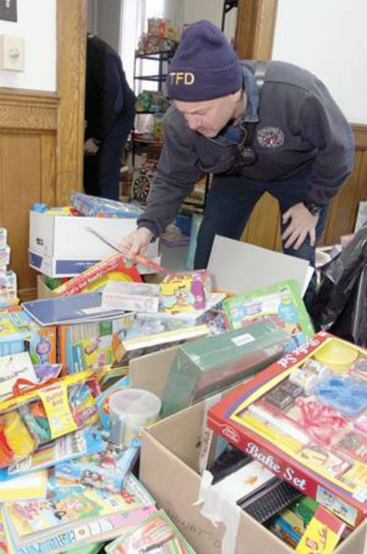 SONJA ZINKE/Register CitizenAndy Corjulo of the Torrington Fire Department was on hand with other members from the department to help sort and pack the thousands of toys being put together for families this Christmas from FISH Inc. The sorting took place on Church Street in Torrington Saturday. Families will be picking up their toys early next week. Purchase a glossy print of this photo and more at www.registercitizen.com