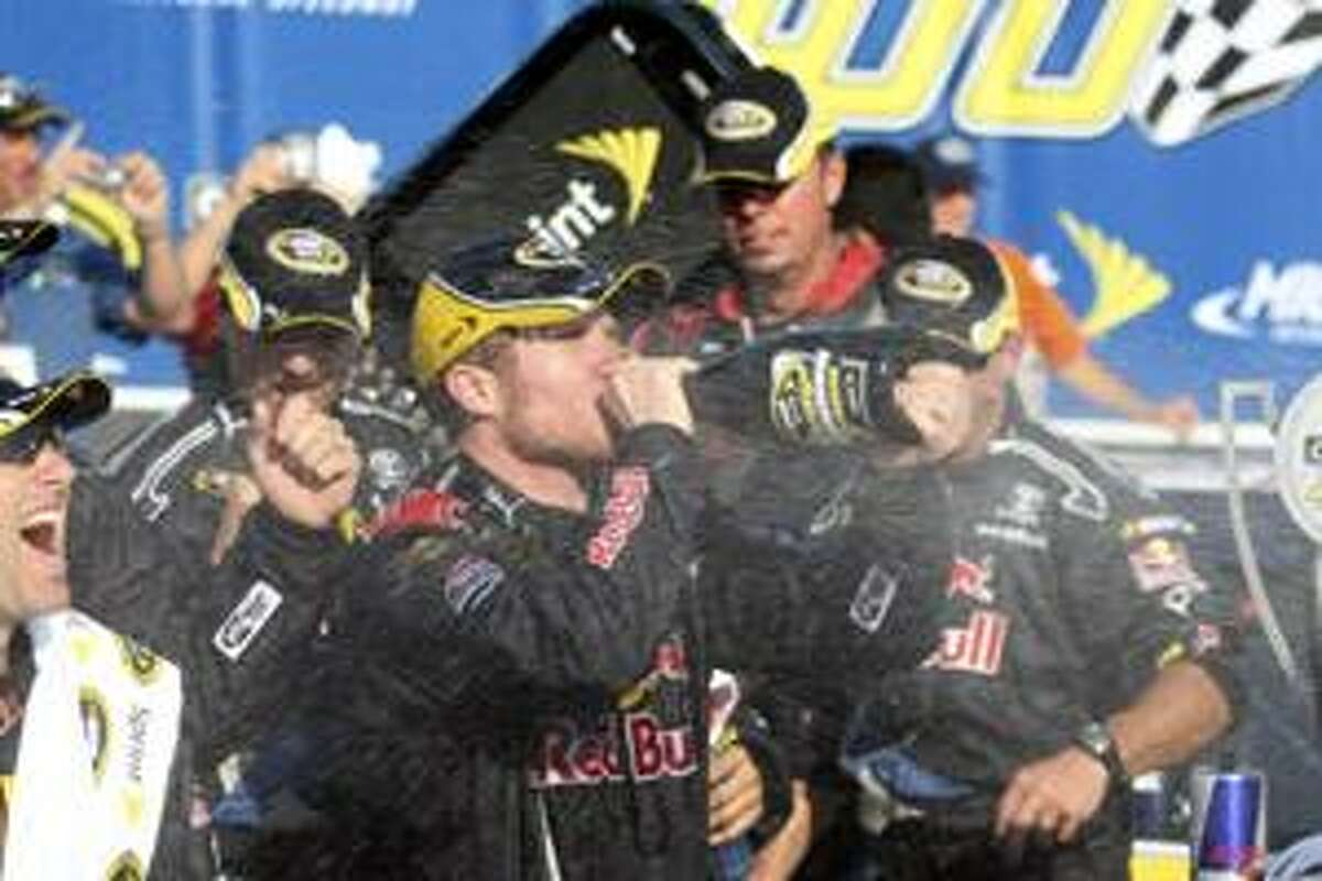 AP Brian Vickers takes a swig of champagne in the winner's circle after the NASCAR Carfax 400 Sprint Cup Series auto race at Michigan International Speedway in Brooklyn, Mich., Sunday.