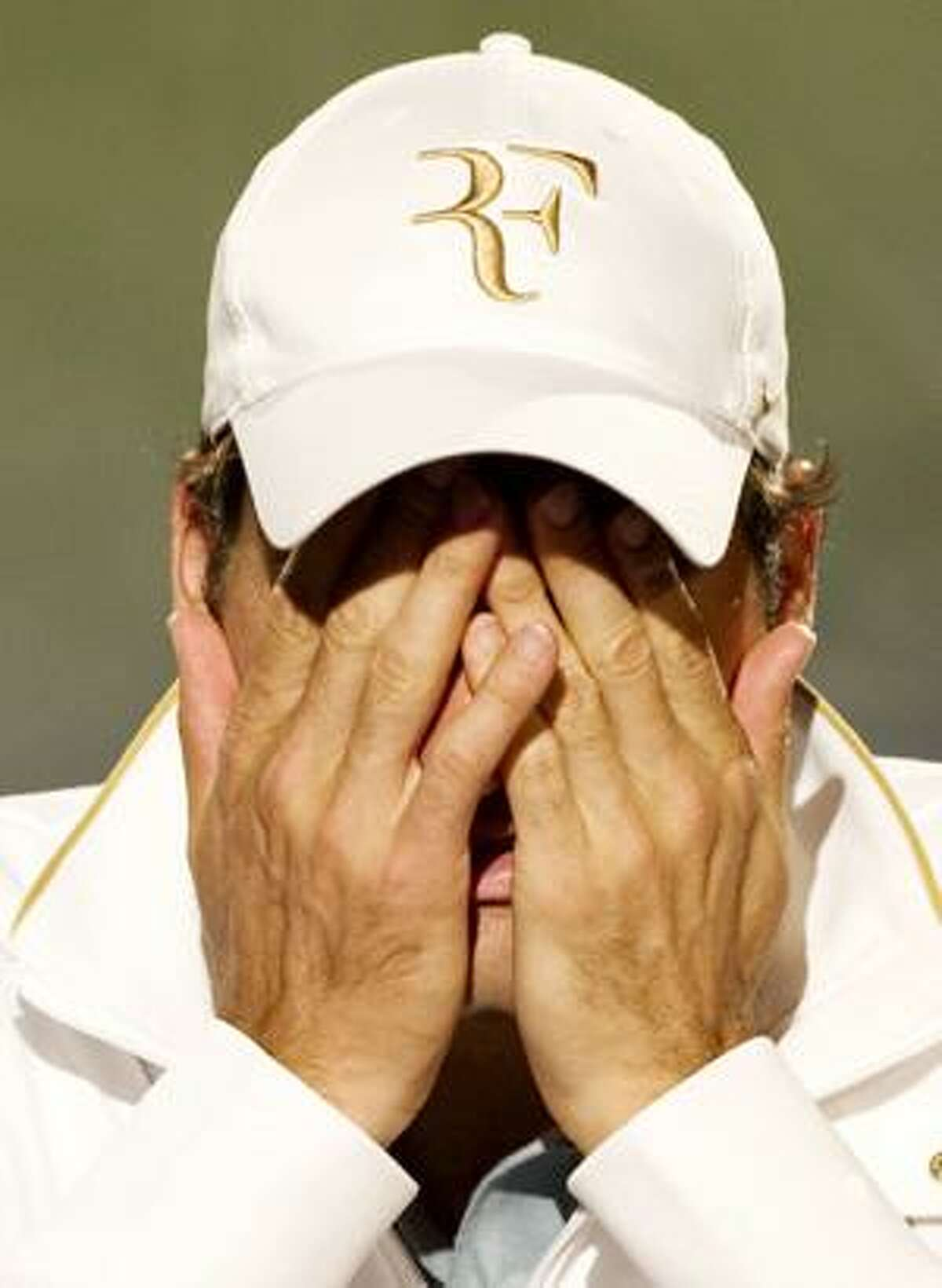AP Defending champion Roger Federer covers his face during his press conference following his loss to Tomas Berdych in their quarterfinal at the All England Lawn Tennis Championships at Wimbledon, Wednesday.