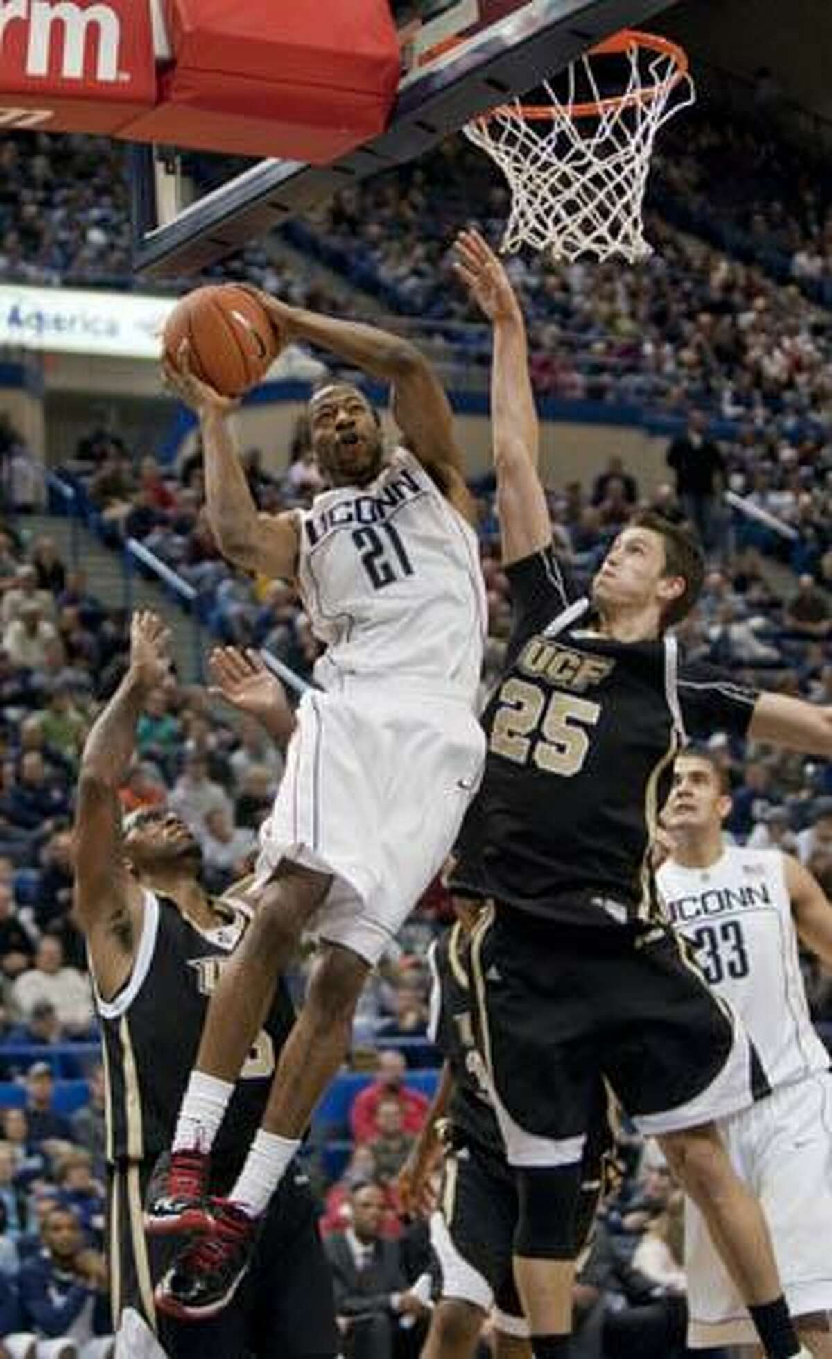 Connecticut's Stanley Robinson, middle, dunks the ball while being guarded by Central Florida's A.J. Tyler, right, and Marcus Jordan, left, during the second half of Connecticut's 60-51 victory over Central Florida Sunday in Hartford.