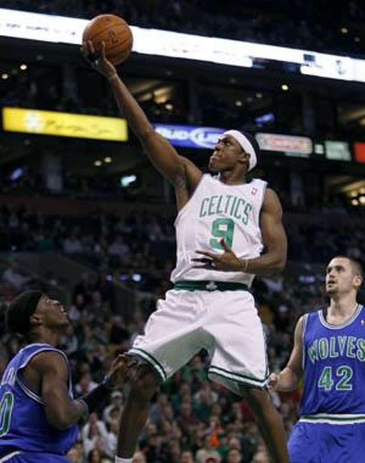 Boston Celtics' Rajon Rondo (9) shoots over Minnesota Timberwolves' Jonny Flynn, left, as Kevin Love (42) looks on during the first quarter Sunday in Boston.