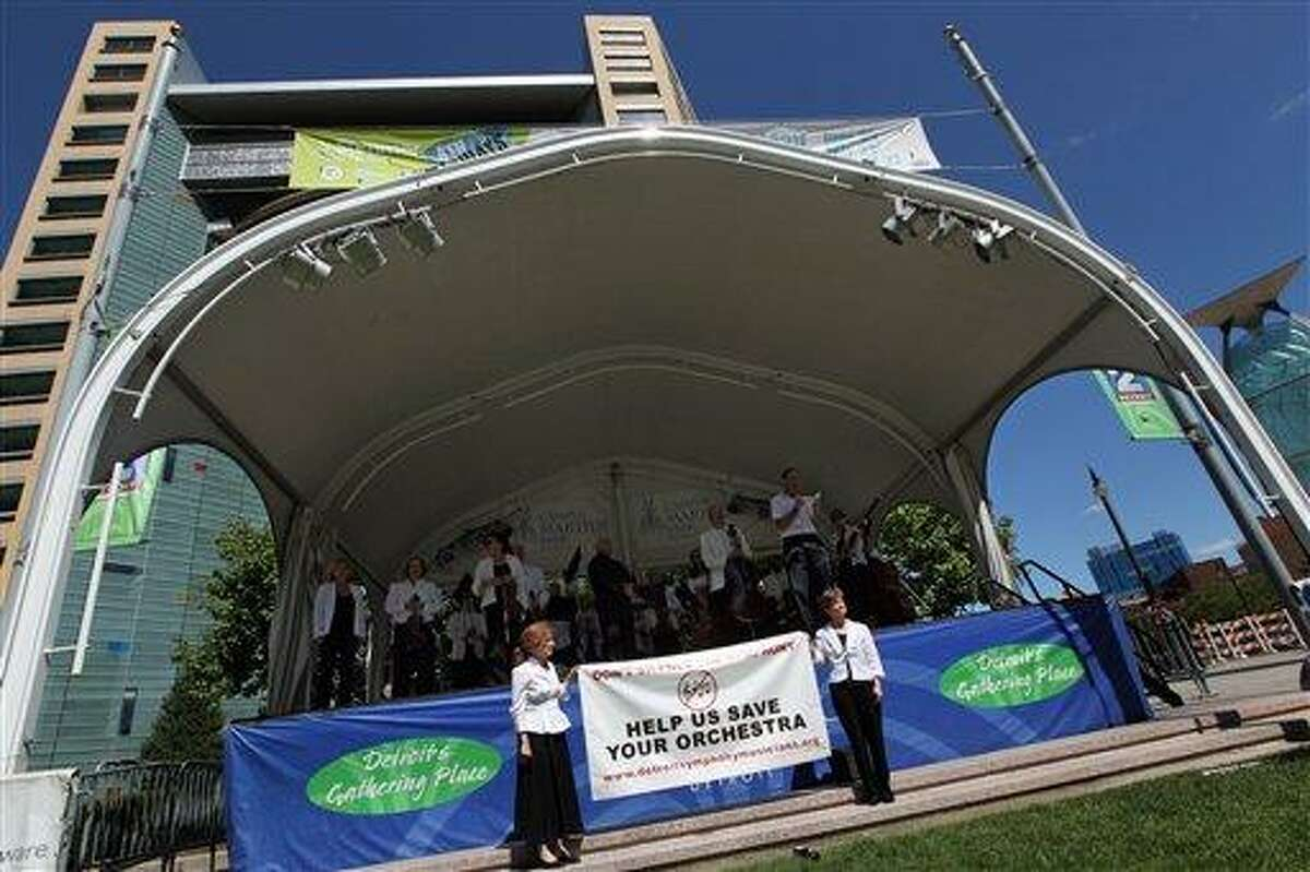 In this Thursday Aug. 26, 2010 photo, musicians of the Detroit Symphony Orchestra stand onstage after a free brief lunchtime concert at Campus Martius Park in Detroit. They held the performance to raise awareness of tense contract negotiations. The musicians voted Saturday to reject a 29 percent first-year pay cut and authorize a strike should contract talks fail. The union offered to take a 22 percent pay cut in the first year of a three-year agreement. (AP Photo/Detroit Free Press, Brian Kaufman) DETROIT NEWS OUT, MAGS OUT, NO SALES, MANDATORY CREDIT
