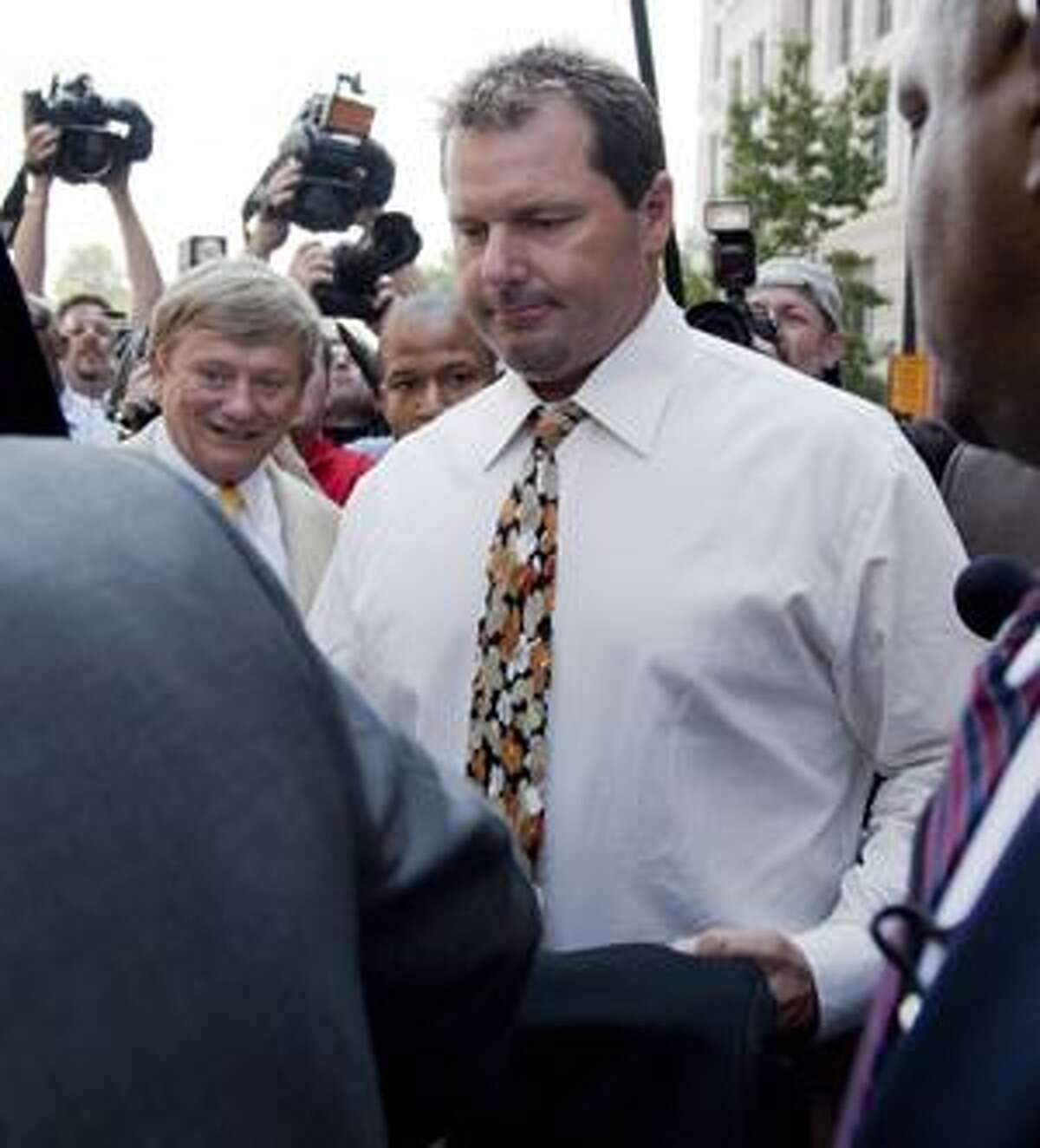 Seven-time Cy Young winner, baseball pitcher Roger Clemens leaves federal court in Washington, Monday, Aug. 30, 2010, after pleading not guilty to charges of lying to Congress about whether he used steroids or human growth hormone. His attorney Rusty Hardin is at left. (AP Photo/Evan Vucci)