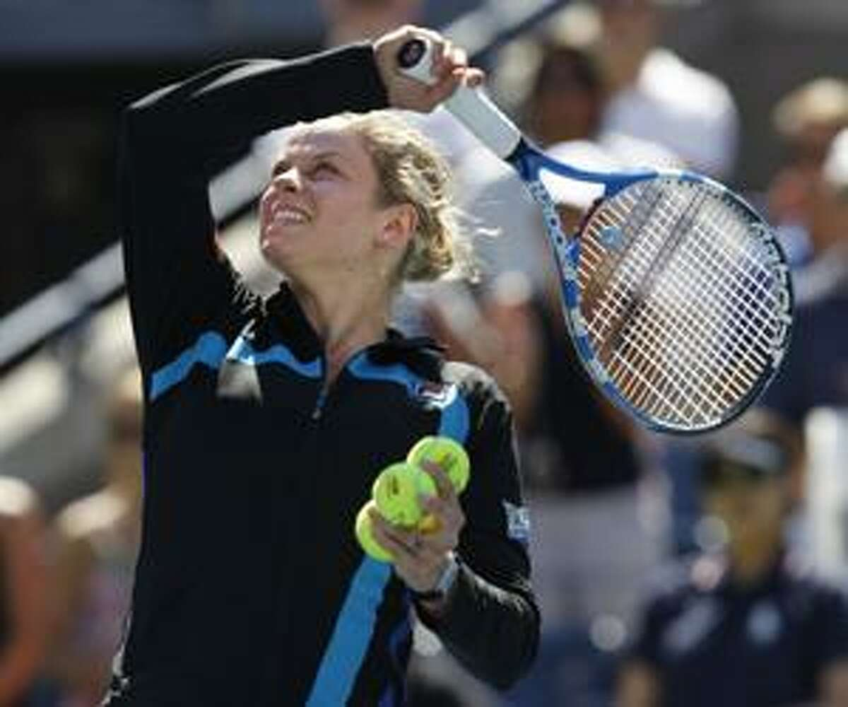 Kim Clijsters of Belgium hits balls into the crowd after she won her match against Greta Arn of Hungary during the first round of the U.S. Open tennis tournament in New York, Monday, Aug. 30, 2010. Clijsters won the match 6-0, 7-5. (AP Photo/Kathy Willens)