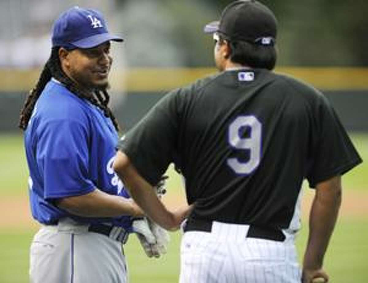Los Angeles Dodgers' Manny Ramirez, left, talks with Colorado Rockies' coach, Vinny Castillo prior to a baseball game at Coors Field in Denver, Colo. on Saturday, Aug. 27, 2010. (AP Photo/ Matt McClain)
