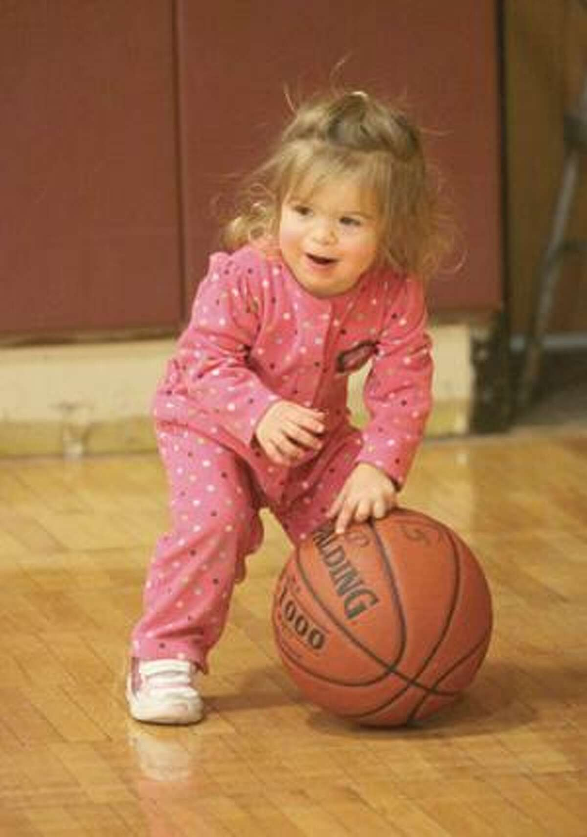 Avalee Fritch, nearly two, plays with a basketball in the Torrington High School gym Friday evening during a girls game. Purchase a glossy print of this photo and more at www.registercitizen.com