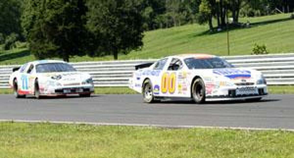 HENRY MOORE/Register Citizen Ryan Truex (00) leads Eddie MacDonald into turn 1 for the final time during the NASCAR Camping World 200 East Mohegan Sun 200 Saturday at Lime Rock Park.