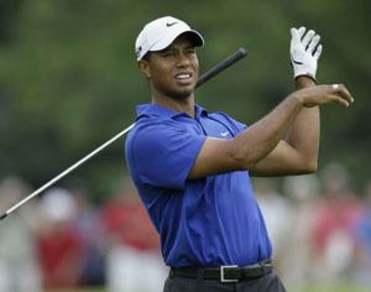 AP Tiger Woods drops his club after his approach shot on the fifth fairway during the third round of the 91st PGA Championship at the Hazeltine National Golf Club in Chaska, Minn., Saturday.