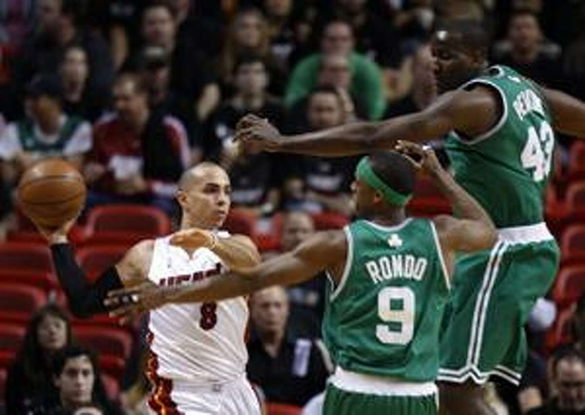 Miami Heat's Carlos Arroyo (8) looks to pass the ball as Boston Celtics players Kendrick Perkins (43) and Rajon Rondo (9) apply pressure in the first half during Game 3 in the first round of their NBA basketball playoff series in Miami, Friday, April 23, 2010. (AP Photo/J Pat Carter)