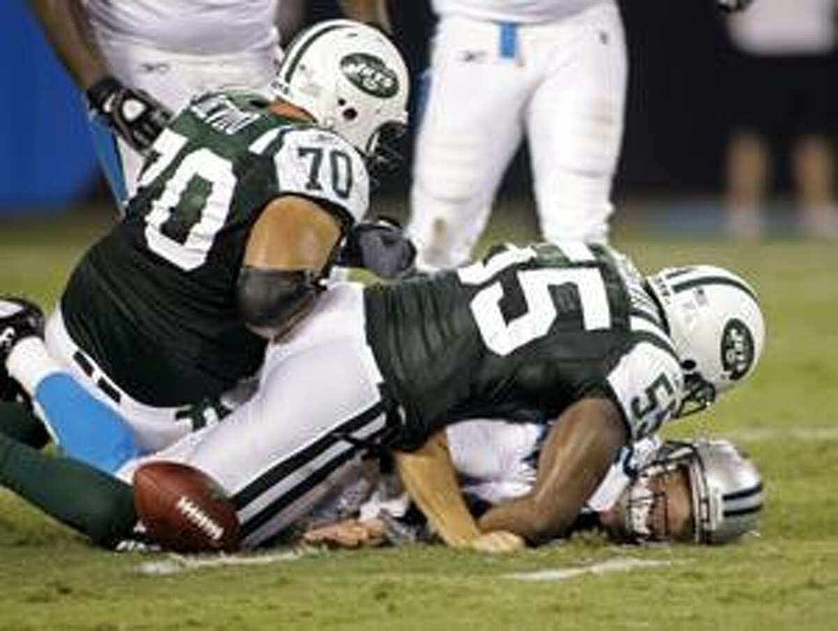 Carolina Panthers' Jimmy Clausen, bottom, loses the ball as he is sacked by New York Jets' Jamaal Westerman (55) and Mike Devito (70) in the fourth quarter of the Jets' 9-3 win in a preseason NFL football game in Charlotte, N.C., Saturday, Aug. 21, 2010. The play was ruled dead and the Panthers retained the ball. (AP Photo/Rick Havner)
