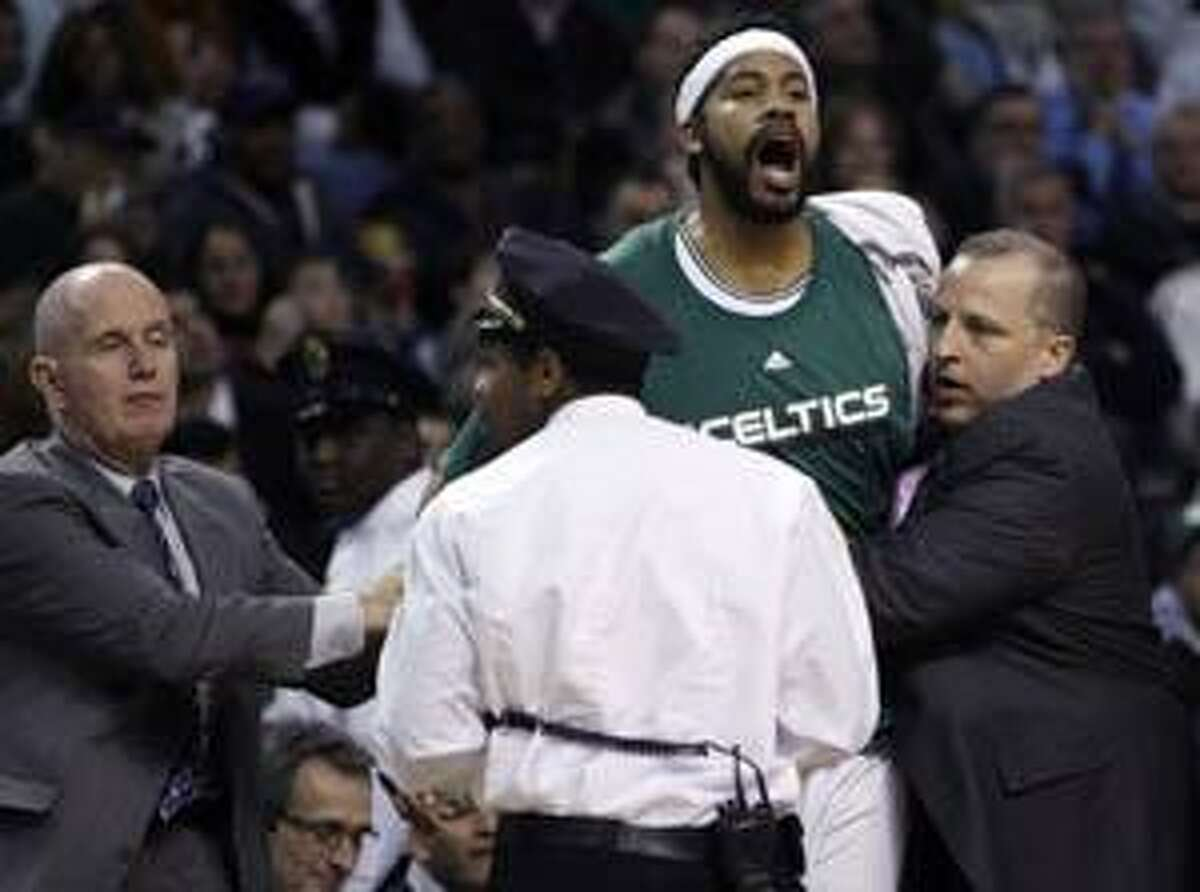 AP Boston Celtics center Rasheed Wallace is restrained by team officials as he yells with a referee after getting ejected following a technical foul call against the Philadelphia 76ers during Friday night's game in Boston.