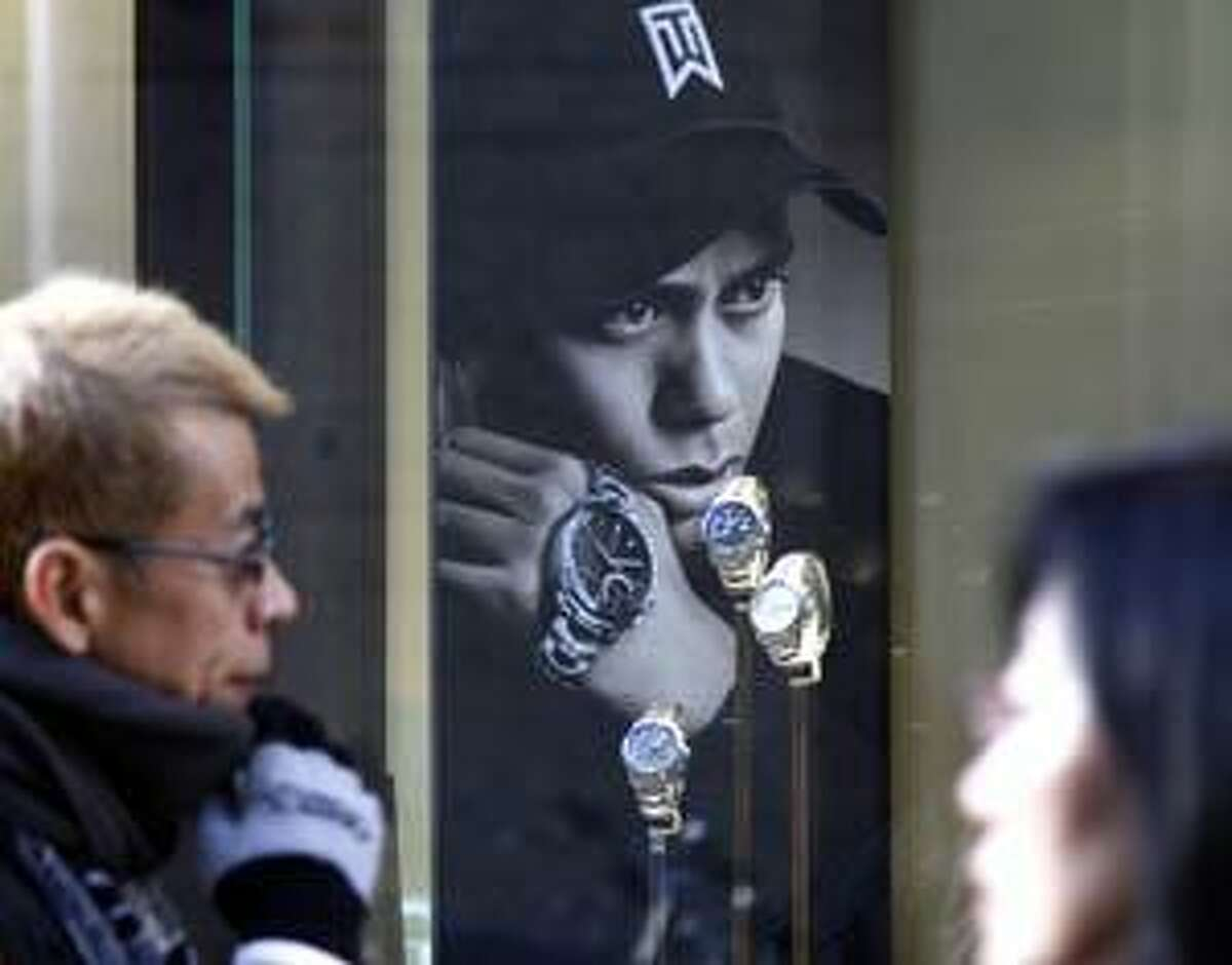 AP People walk by a Swiss watch shop displaying watches along with U.S. golfer Tiger Woods' portrait in Tokyo on Tuesday. Swiss watch maker Tag Heuer says it will not use Tiger Woods' image in advertising campaigns in the United States for the foreseeable future.