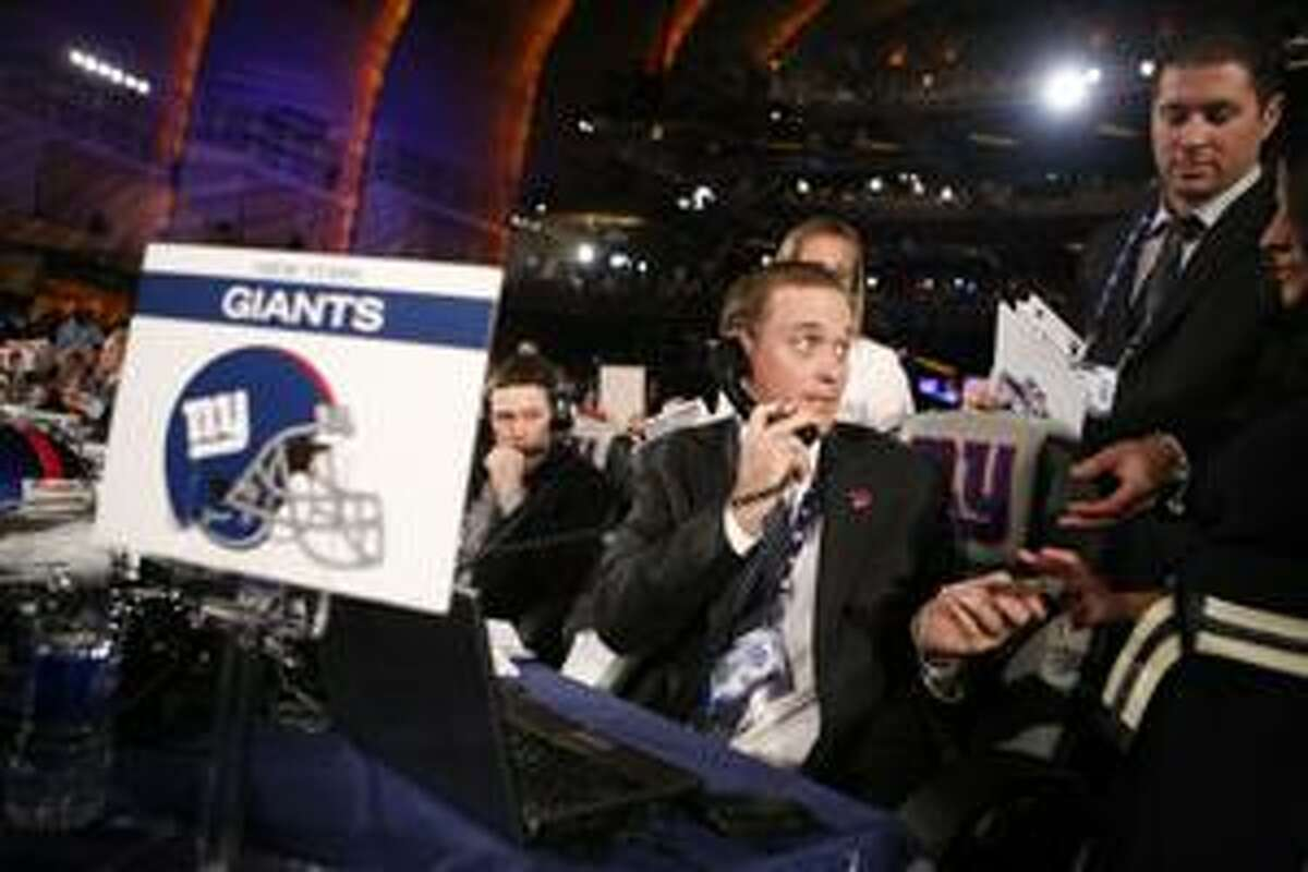 A representative of the New York Giants hands over the team's third round pick during the NFL football draft at Radio City Music Hall Friday, April 23, 2010 in New York. (AP Photo/Jason DeCrow)