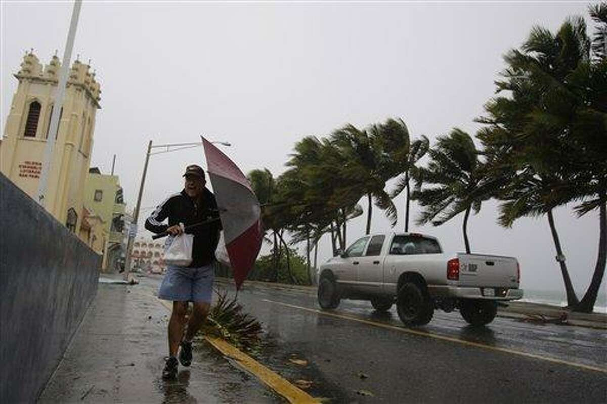 Luis Colon uses an umbrella to shield himself from rain and wind caused by the approaching Hurricane Earl in San Juan, Puerto Rico, Monday Aug. 30, 2010. (AP Photo/Andres Leighton)