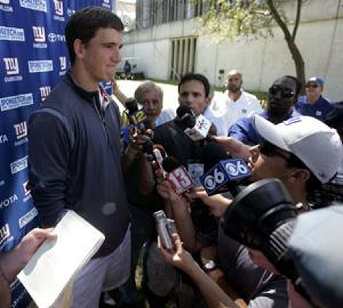 AP New York Giants quarterback Eli Manning talks to reporters during training camp in Albany, N.Y., on Friday. Manning finally signed the six-year extension that will make him the NFL's highest paid player with an average salary of roughly $15.3 million. The Giants announced the signing on Friday morning after spending more than a week completing the deal that will keep Manning with the team through the 2015 season.