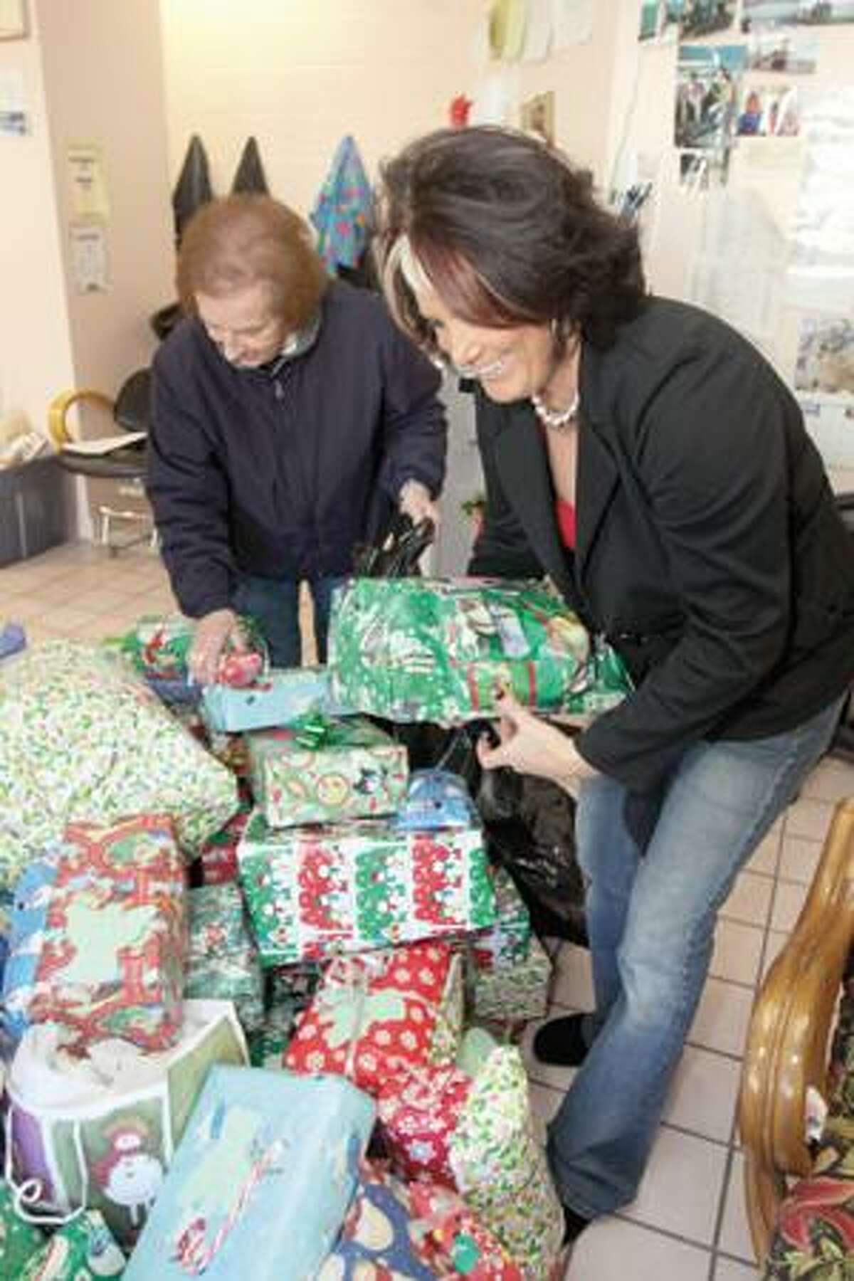 SONJA ZINKE/Register CitizenRight, Susan Gagnon, owner of Hair Dr. on East Main Street in Torrington, helps Special Events Coordinator for Torrington Area Youth Service Bureau Joyce Reilly pack up presents from under the wish tree at the salon. Hair Dr. hosted the wish tree with 150 wishes for gifts from area children which were filled by customers at the salon. Purchase a glossy print of this photo and more at www.registercitizen.com