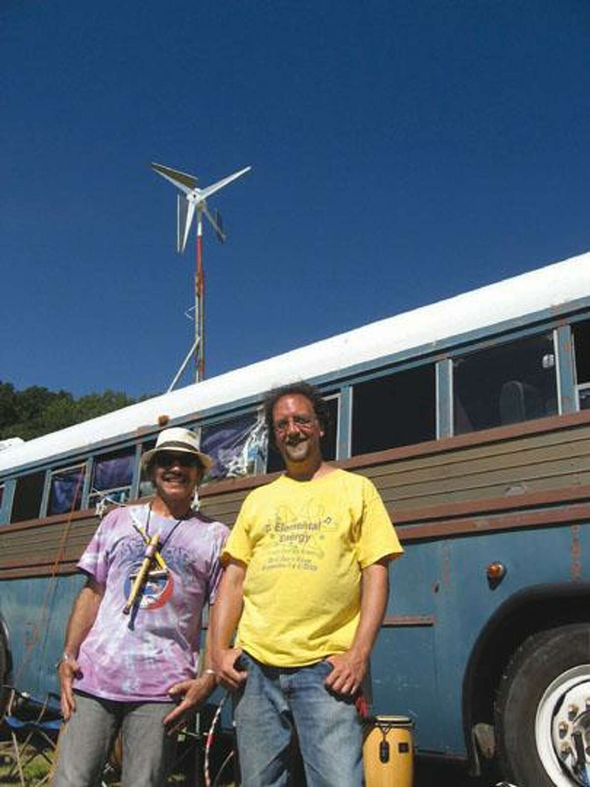 Ray Gelinas (left) and Joe Geloso (right) stand in front of Gelinas' bus, which is partially run by a wind turbine. The two friends generated the idea for the Clean Energy Expo, held at Lorenz Studios in Morris on Aug. 28 and 29, with the idea of fusing arts and clean energy interests.