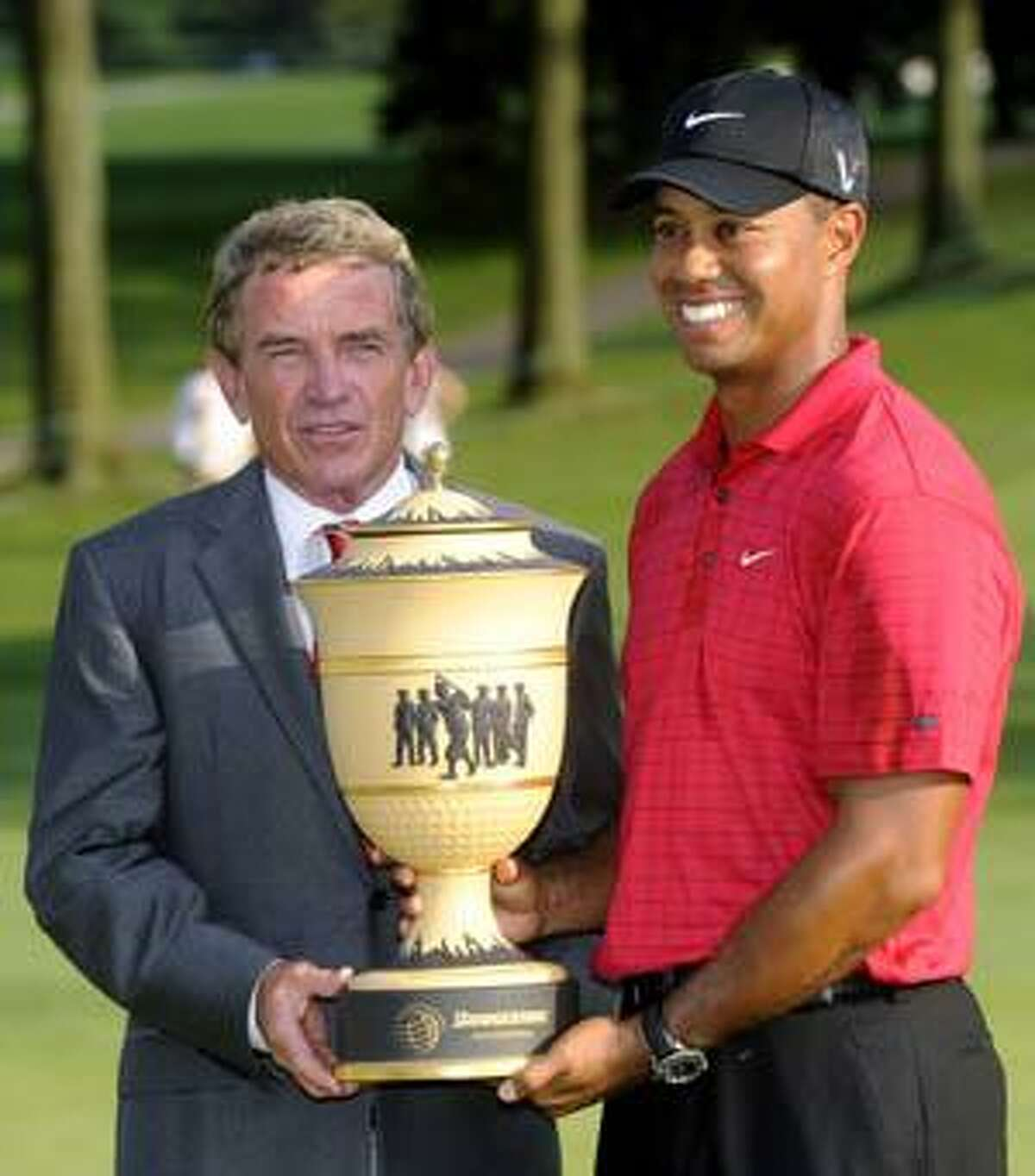 AP Tiger Woods, right, holds the Bridgestone Invitational trophy with PGA Tour commissioner Tim Finchem, after Woods won the golf tournament in Akron, Ohio, on Aug. 9. Finchem says Tiger Woods' indefinite leave doesn't spell
