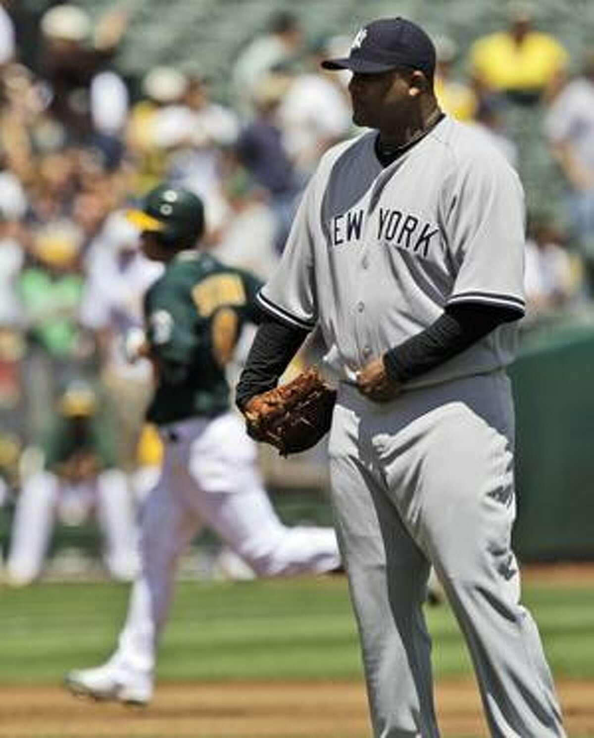 New York Yankees starting pitcher CC Sabathia waits as Oakland Athletics' Kurt Suzuki, left, rounds the bases on a three-run home run during the third inning of a baseball game in Oakland, Calif., Thursday, April 22, 2010. (AP Photo/Marcio Jose Sanchez)