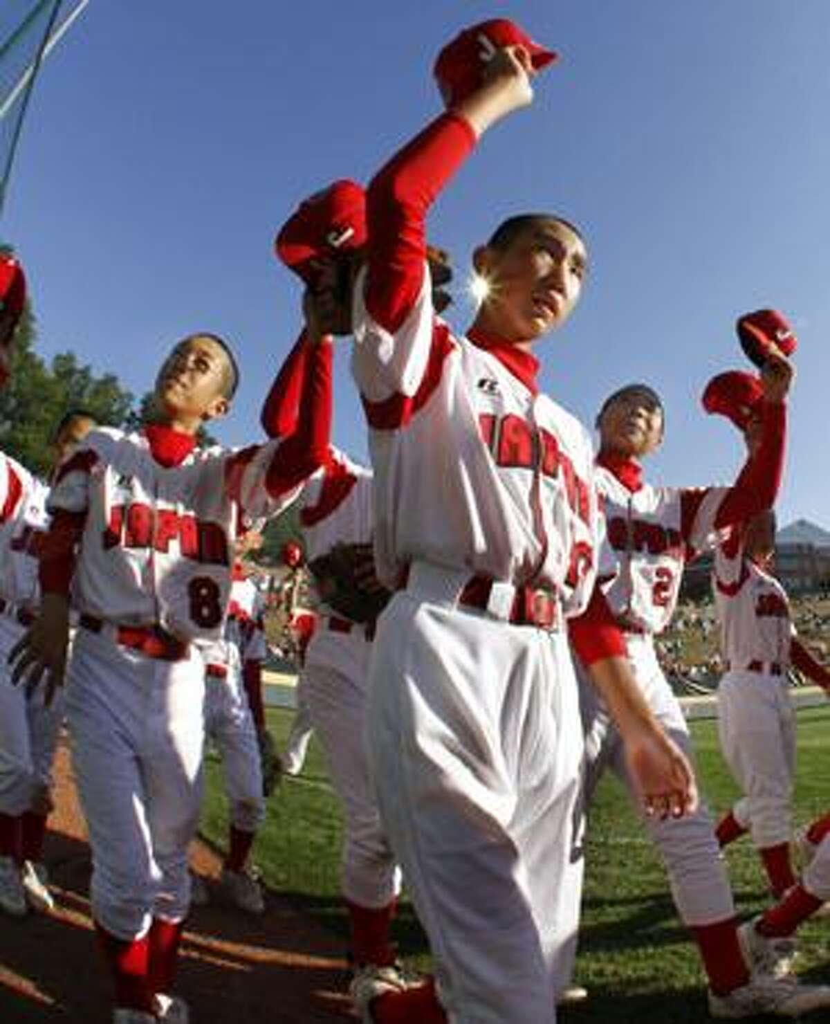 AP In this photo made with a fisheye lens, Tokyo, Japan's Ichiro Ogasawara (8), Ryo Motegi, center, and Kaname Shinozaki, right, take part in a team victory lap around Lamade Stadium after Japan beat Waipahu, Hawaii, 4-1 in the Little League World Series championship game in South Williamsport, Pa., Sunday.