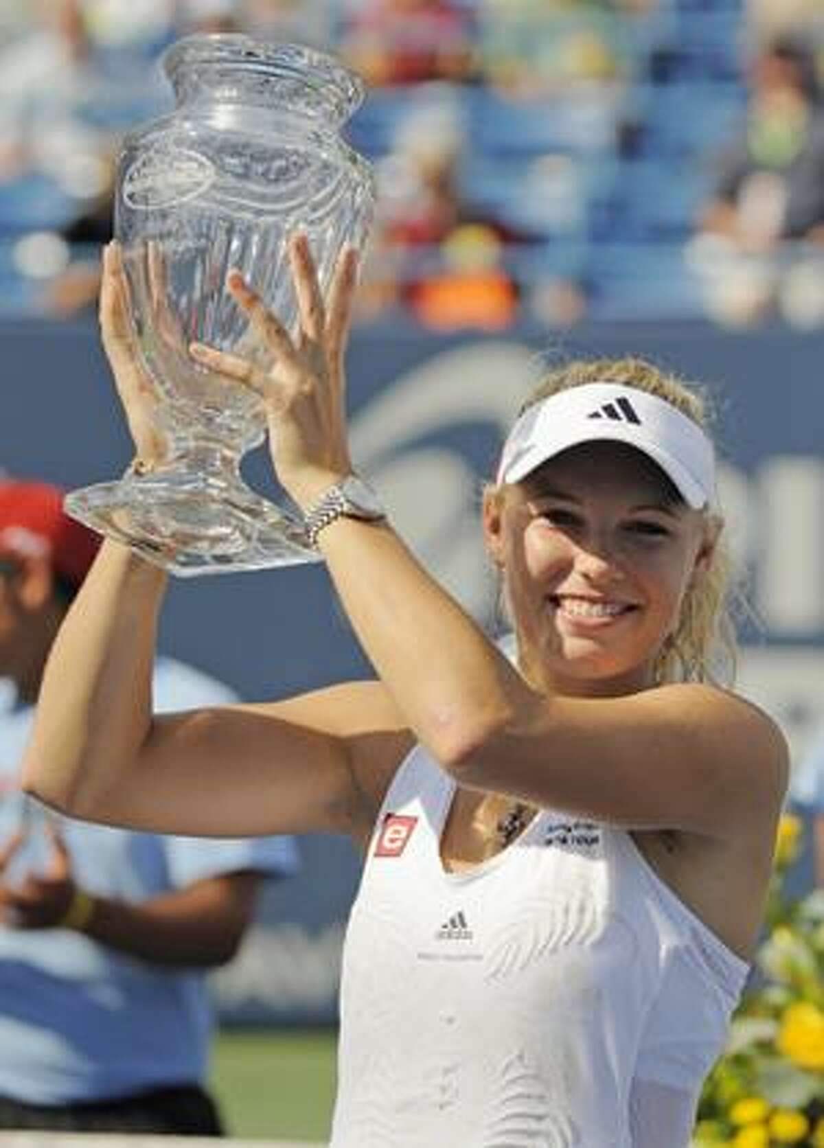 AP Caroline Wozniacki, of Denmark, lifts her trophy after defeating Nadia Petrova, of Russia, 6-3, 3-6, 6-3, in the women's final of the Pilot Pen tennis tournament in New Haven, on Saturday.