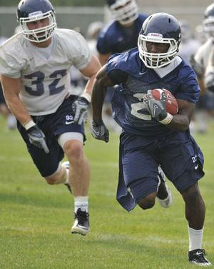 AP Connecticut's Jordan Todman, right, is pursued by Scott Lutrus, left, during football practice in Storrs on Aug. 9. Todman and Lutrus will both be key players for the Huskies this season. UConn enters with high expectations for itself. Photo: ASSOCIATED PRESS / FR125654 AP
