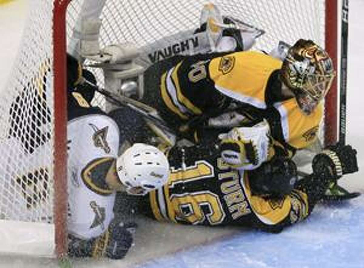 Buffalo Sabres center Cody McCormick, left, slams into Boston Bruins goalie Tuukka Rask, right, of Finland, and left wing Marco Sturm, of Germany, pushing them into the net during the third period of a first-round NHL hockey playoff game in Boston, Wednesday, April 21, 2010. McCormick was charged with goalie interference on the play. (AP Photo/Charles Krupa)