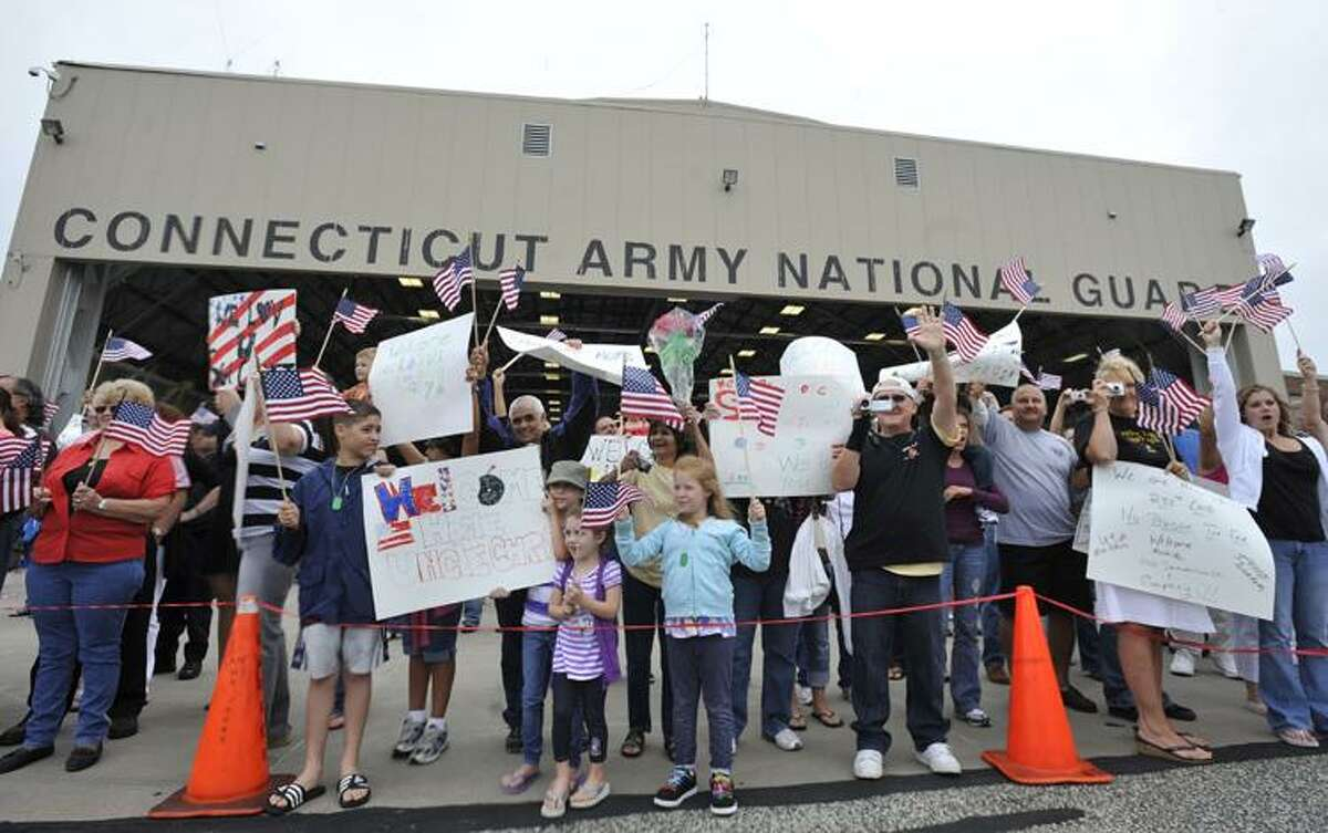 Family and friends wave to a plane carrying members of the 250th Engineer Co. at the Army aviation support facility in Windsor Locks, Conn., Wednesday, Aug. 25, 2010. About 110 soldiers of the 250th Engineer Co., Connecticut National Guard who were deployed to Iraq last winter have returned home. (AP Photo/Jessica Hill)