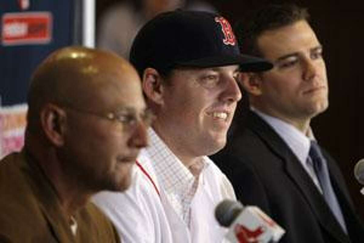 Newly-acquired Boston Red Sox pitcher John Lackey, center, is flanked by manager Terry Francona, left, and general manager Theo Epstein during a news conference Wednesday at Fenway Park in Boston.