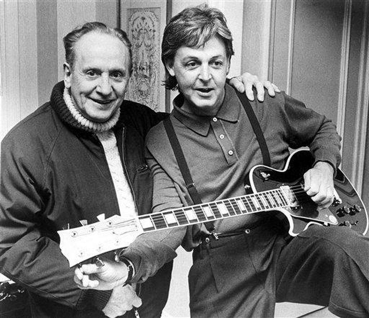 FILE - In this May 3, 1988 file photo, Paul McCartney, right, tries out a custom-made left handed
