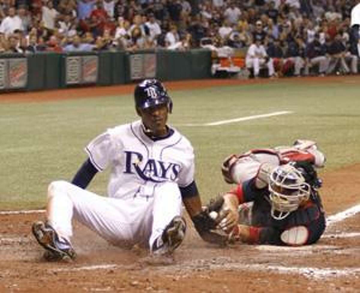 Boston Red Sox catcher Victor Martinez, right, makes the tag at home on Tampa Bay Rays' B.J. Upton, left, who tried to reach from second on a hit by Jason Bartlett, during the sixth inning of a baseball game in St. Petersburg, Fla., Friday, Aug. 27, 2010. (AP Photo/Reinhold Matay)
