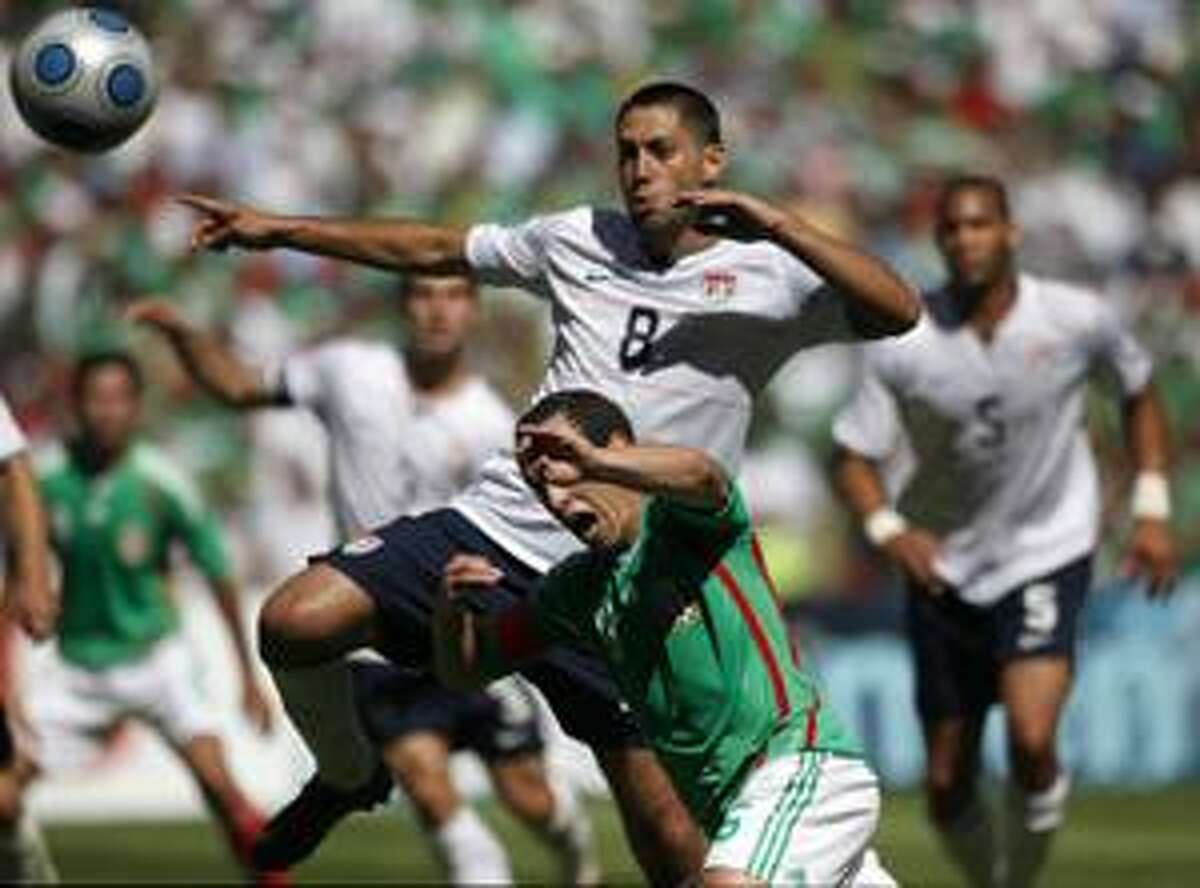 Clint Dempsey, top, of the U.S. national soccer team, fights for the ball against Gerardo Torrado of Mexico during a World Cup qualifier at the Aztec Stadium in Mexico City Wednesday.
