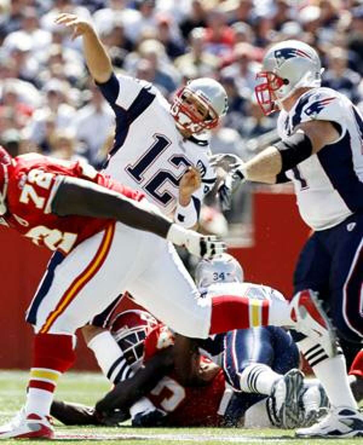 In this Sept. 7, 2008, file photo, New England Patriots quarterback Tom Brady (12) has his leg buckled by Kansas City Chiefs safety Bernard Pollard, bottom, during the first quarter at Gillette Stadium in Foxboro, Mass. The tackle Pollard was legal, though the NFL has since outlawed the type of lunge that hurt Brady.