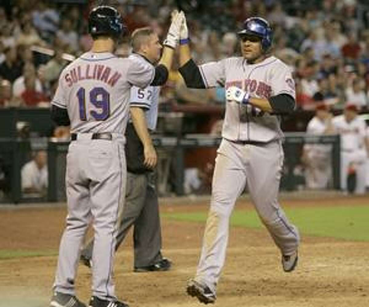 New York Mets' Fernando Tatis, right, high fives teammate Cory Sullivan (19) after scoring on an RBI single by Luis Castillo against the Arizona Diamondbacks during the eighth inning Wednesday in Phoenix.