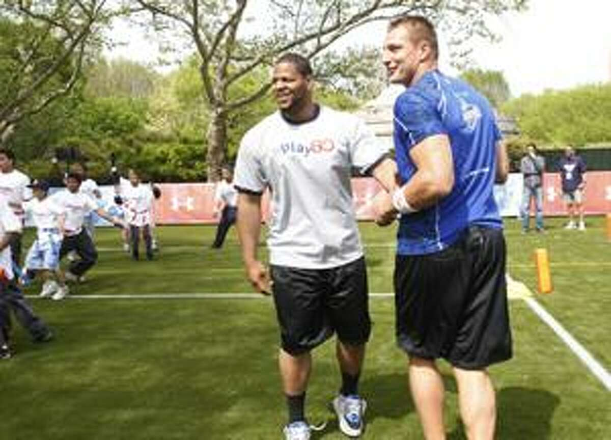 NFL draft prospects Ndamukong Suh, left, of Nebraska, and Rob Gronkowski, of Arizona, play football with youngster during a youth football clinic at Central Park in New York, Wednesday, April 21, 2010. (AP Photo/Seth Wenig)