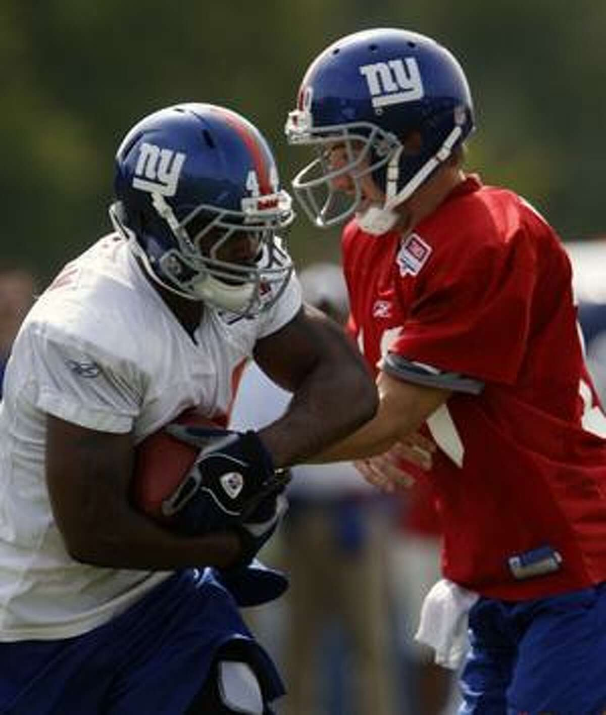 New York Giants running back Ahmad Bradshaw (44) takes a handoff from quarterback Eli Manning during training camp in Albany, N.Y., Wednesday.