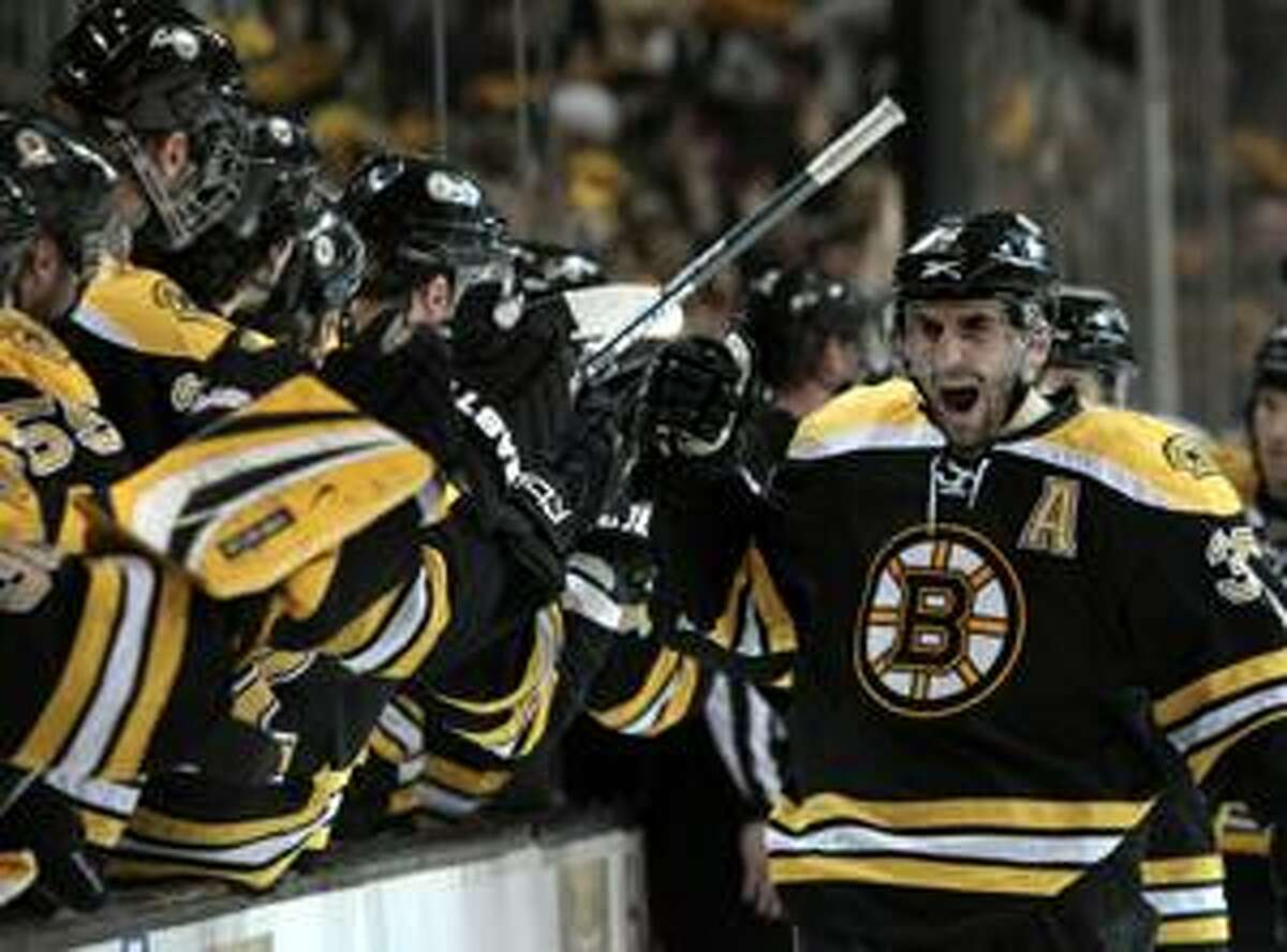 Boston Bruins center Patrice Bergeron (37) celebrates his goal as he skates back to the bench during the third period of Game 3 against the Buffalo Sabres in an NHL hockey playoff series in Boston on Monday, April 19, 2010. (AP Photo/Elise Amendola)