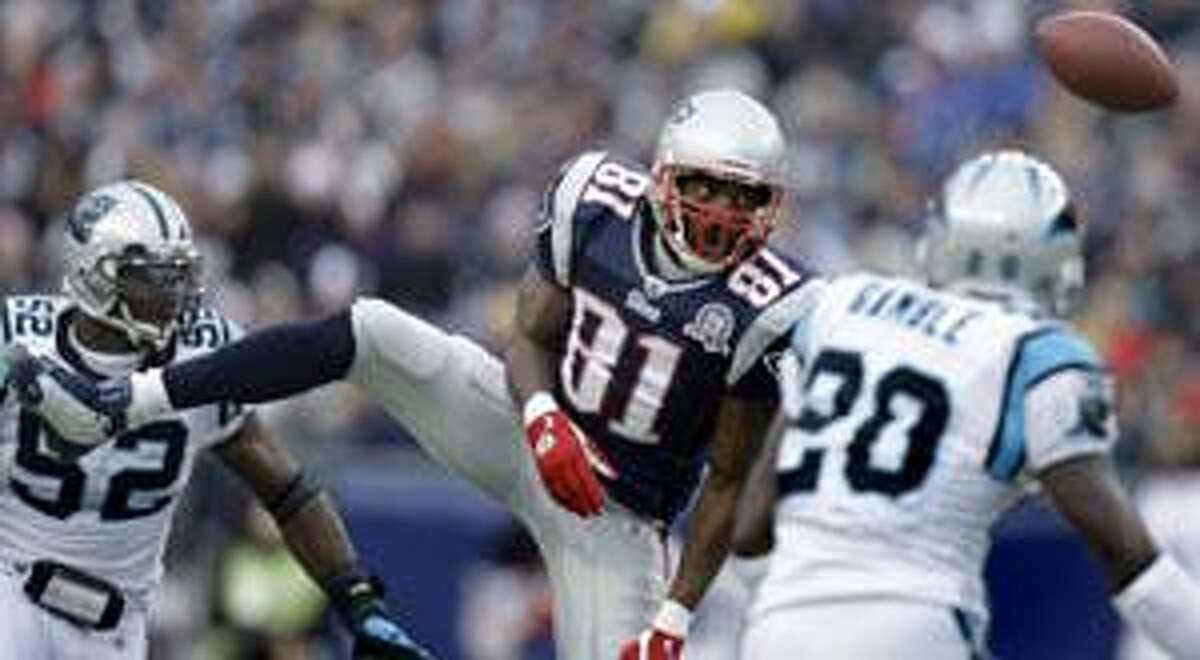 New England Patriots wide receiver Randy Moss (81) loses control of the ball as he is pressured by Carolina cornerback Chris Gamble (20) and linebacker Jon Beason (52) Sunday in Foxboro, Mass.