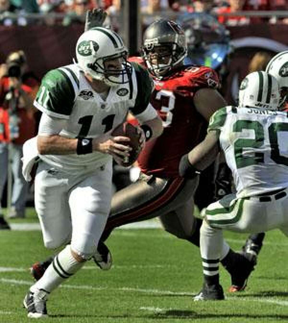 New York Jets quarterback Kellen Clemens (11) scrambles as Jets' Thomas Jones, right, puts a block on Tampa Bay Buccaneers defensive tackle Roy Miller (93) during the first quarter Sunday in Tampa, Fla.