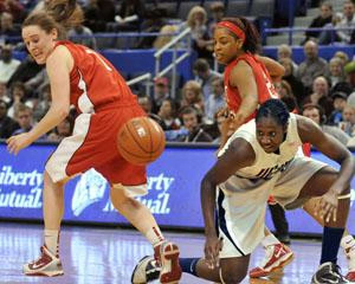Connecticut's Tina Charles, right, and Hartford's Jackie Smith, left, chase down a loose ball as Hartford's Ruthanne Doherty looks on during their game Dec. 10 in Hartford.