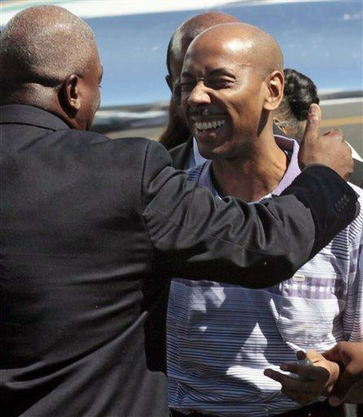 Aijalon Gomes is greeted by family members after arriving with former President Jimmy Carter at Logan International Airport in Boston, Aug. 27, 2010. Carter flew to the North Korean capital, Pyongyang, this week on a private mission to secure a pardon for the 31-year-old American who was detained in January after crossing into the country from China. (AP Photo/Winslow Townson)