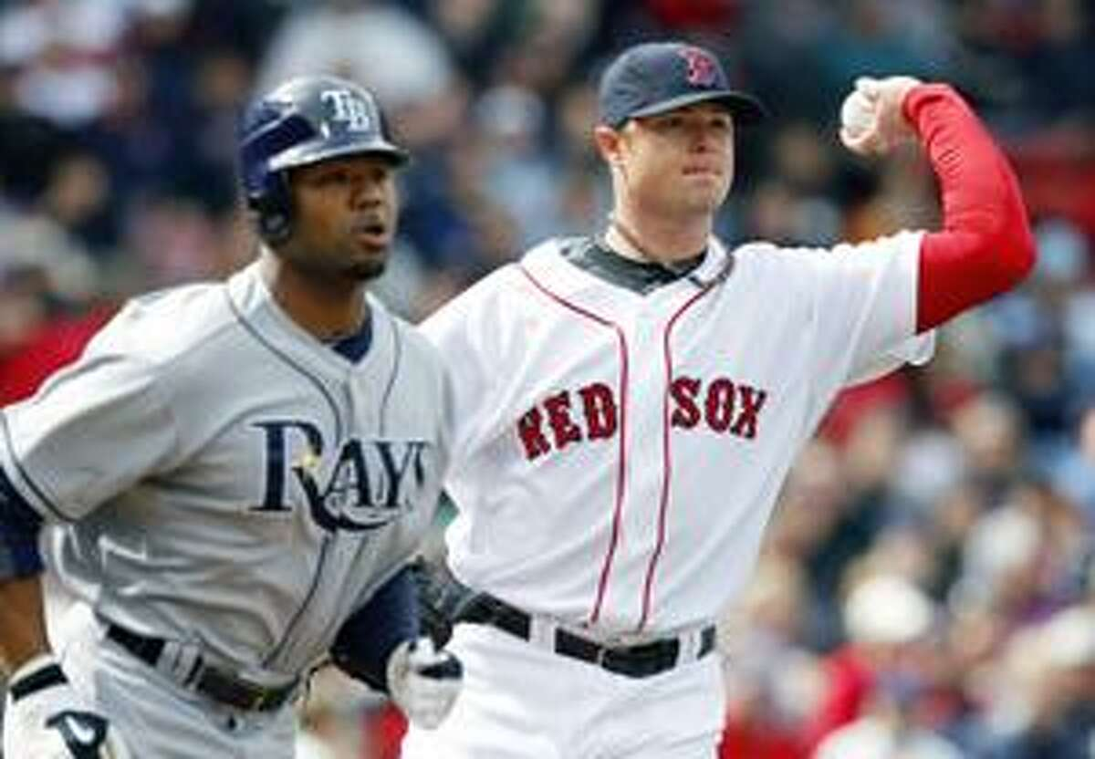 Boston Red Sox's Jon Lester, right, throws to first on a sacrifice bunt by Tampa Bay Rays' Carl Crawford, left, in the third inning of a baseball game, Sunday, April 18, 2010, in Boston. (AP Photo/Michael Dwyer)