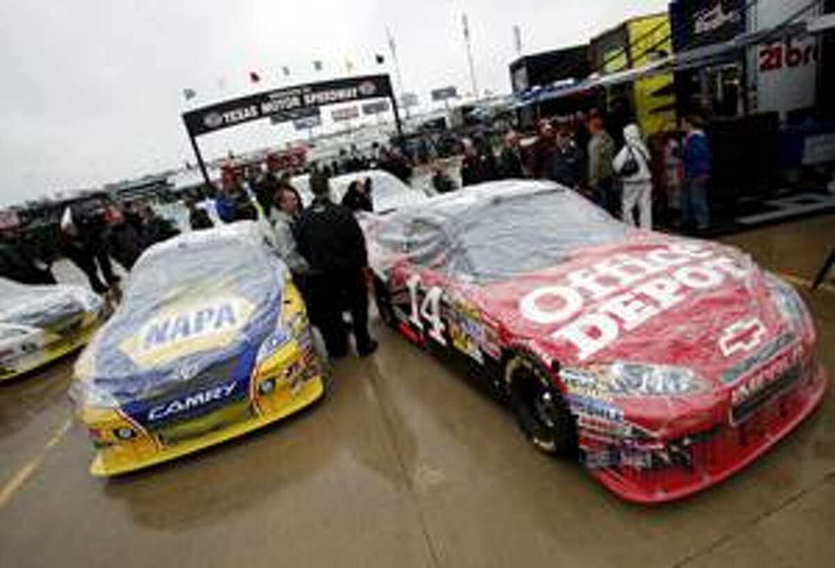 Crew members for the Martin Truex, Jr. car, left, and the Tony Stewart car, right, wait in line with the cars covered in plastic to protect them from drizzle as they wait for inspection before the Nascar Sprint Cup Race at Texas Motor Speedway on Sunday, April 18, 2010 in Fort Worth, Texas. (AP Photo/Sharon Ellman)