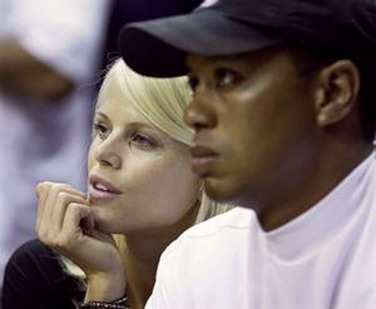 FILE - In this June 11, 2009 file photo, Elin Nordegren talks to her husband, golfer Tiger Woods during the first quarter of Game 4 of the NBA basketball finals in Orlando, Fla. Nordegren said she has