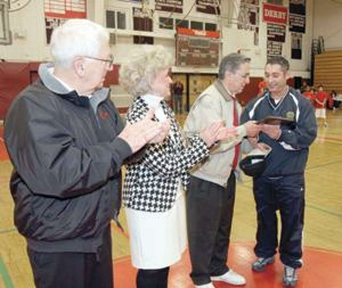 SONJA ZINKE/Register CitizenTorrington Police Officer Tony Pietrafesa, right awards Andy Pace with a plaque of appreciation from PAL/Elks Basketball League Saturday at the Torrington High School. Left Lou Zanderiago also received a plaque. Doris Richards, center was on hand to accept the honor for her brother Frankie Russo. Joseph Killany was also honored but was not able to attend. Purchase a glossy print of this photo and more at www.registercitizen.com
