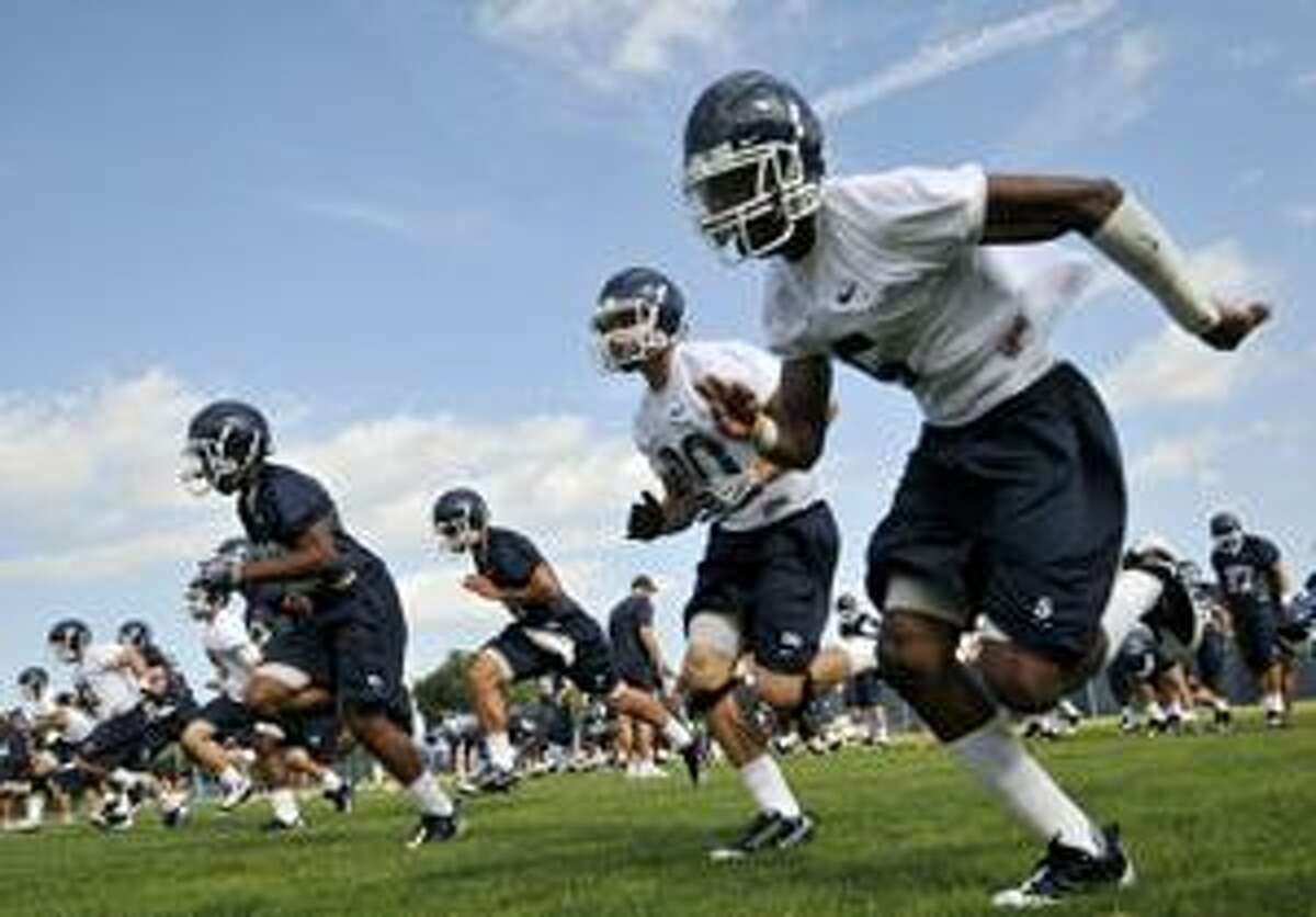 Connecticut football players sprint across the practice field on the first day of the team's practice Monday in Storrs.