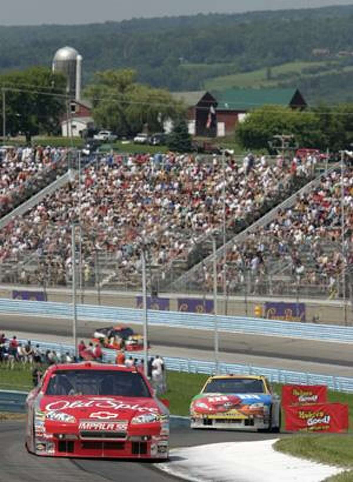 Tony Stewart leads Kyle Busch through the esses during the NASCAR Sprint Cup Series' Heluva Good! Sour Cream Dips at The Glen Monday in Watkins Glen, N.Y. Stewart won the race, and Busch finished fourth.