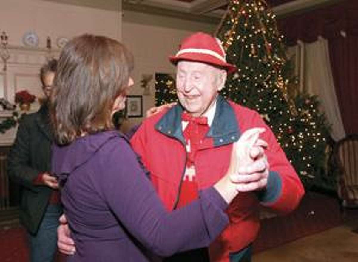Torrington Recreation Director Donna Winn dances with one of the founders of Christmas Village, 94 year old Paul Freedman Friday at the annual Christmas Village Toy Shower held at the Yankee Pedlar.