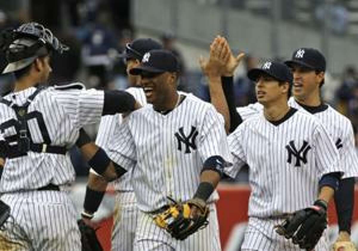 New York Yankees' Jorge Posada, left, celebrates with teammates Robinson Cano, second from left, Ramiro Pena, second from right, and Mark Teixeira, right after their 7-3 win over the Texas Rangers in a baseball game on Saturday, April 17, 2010, in New York. (AP Photo/Frank Franklin II)